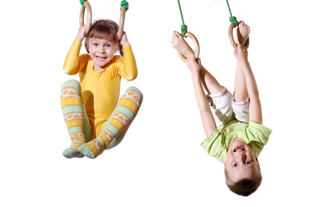 two 4 year old kid hanging on gymnastic rings